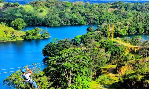Aventurero Deslizándose sobre el Lago Gatún Haciendo un Tour de Canopy en Panamá